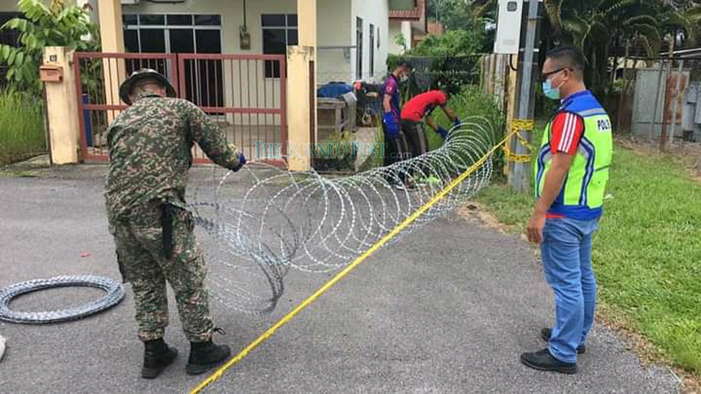 Authorities setting up barbed wires to mark the EMCO areas in Bintulu. — Borneo Post Online pic