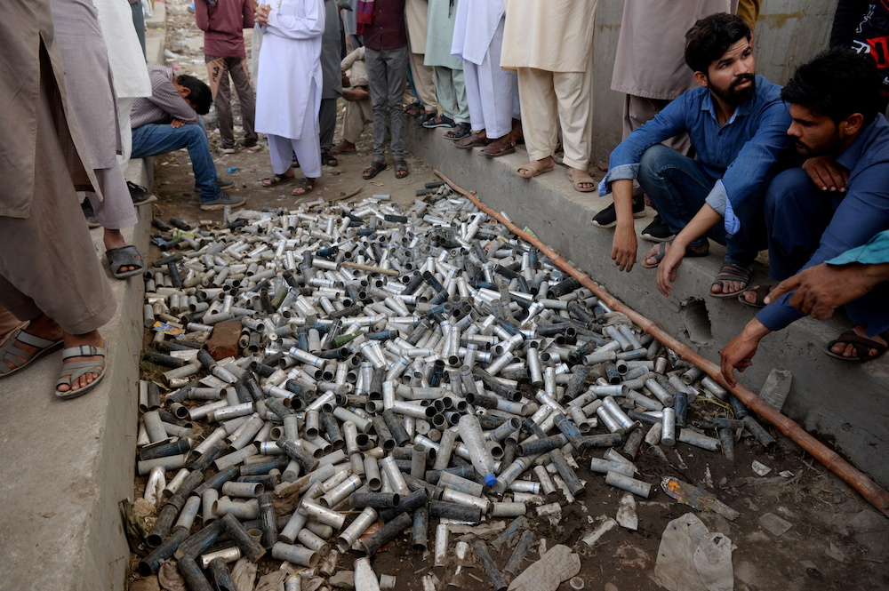 Supporters of the banned Islamist political party Tehrik-e-Labaik Pakistan (TLP) display a pile of used teargas canisters which, according to them, were fired by the police during a protest in Lahore, Pakistan April 19, 2021. — Reuters pic