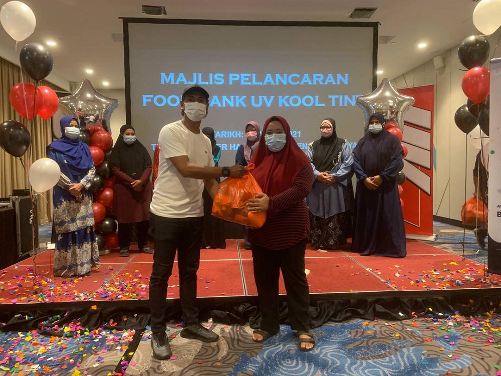 TMK Industries managing director Mohd Fadzli Che Harun (left) presenting a food basket to the poor during the launching of UV Kool Tint's food bank recently. — Picture courtesy of UV Kool Tint