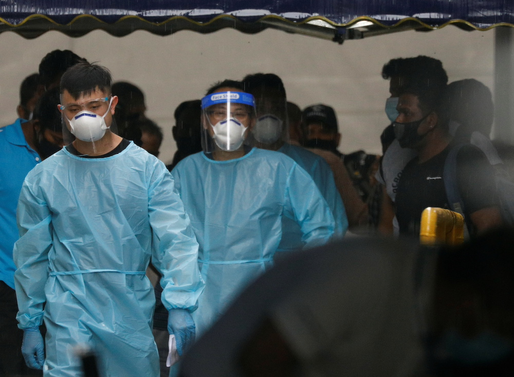 Personnel in protective garment usher a group of migrant workers to take a bus to a government quarantine facility after workers were tested positive for Covid-19 at Westlite Woodlands dormitory in Singapore April 22, 2021. — Reuters pic