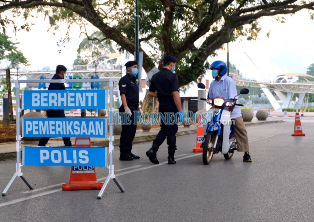 Policemen stopping a motorcyclist at an MCO roadblock near the Kuching Old Courthouse. — Borneo Post Online pic