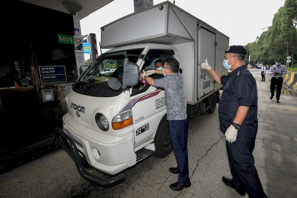 Deputy Minister of National Unity Datuk Seri Ti Lian Ker presenting a pack of lambuk porridge to a driver passing through the highway at the Jalan Duta Toll Plaza in Kuala Lumpur, April 28, 2021. Also present was the Head of the Royal Malaysia Police Traffic Investigation and Enforcement Department, ACP Zulkefly Yahya. — Bernama pic