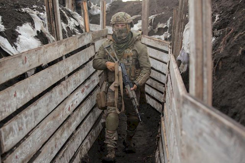 A service member of the Ukrainian armed forces walks with a weapon at fighting positions on the line of separation near the rebel-controlled city of Donetsk, Ukraine April 6, 2021. — Reuters pic