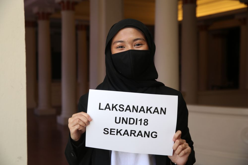 Elisa Shafiqah holds up a sign protesting the delay of Undi18 during a press conference at the Kuala Lumpur and Selangor Chinese Assembly Hall April 2, 2021. — Picture by Choo Choy May