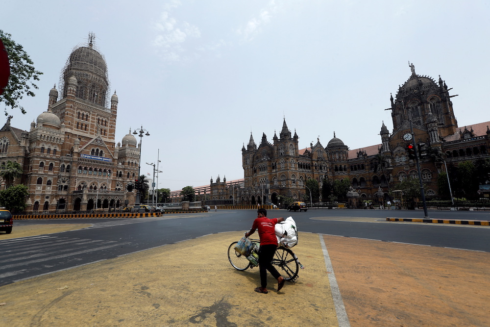 A man walks with his bicycle in front of the Brihanmumbai Municipal Corporation building and the Chhatrapati Shivaji Maharaj Terminus during a weekend lockdown to limit the spread of the coronavirus disease in Mumbai, India, April 10, 2021. — Reuters pi