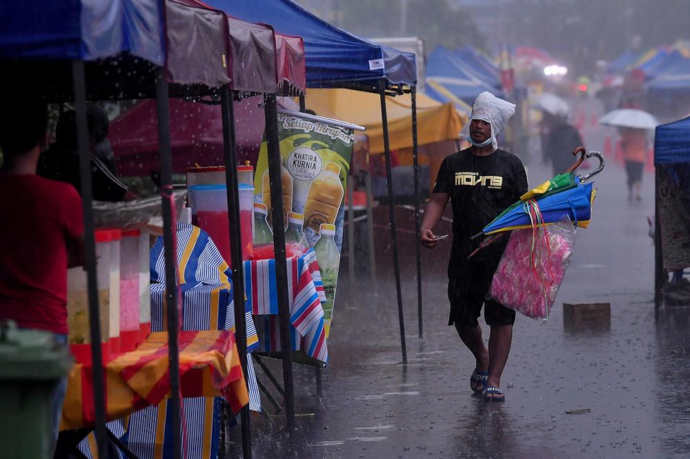 Despite the downpour, people can be seen buying food at the Kampung Baru Ramadan bazaar, April 13, 2021. — Bernama pic
