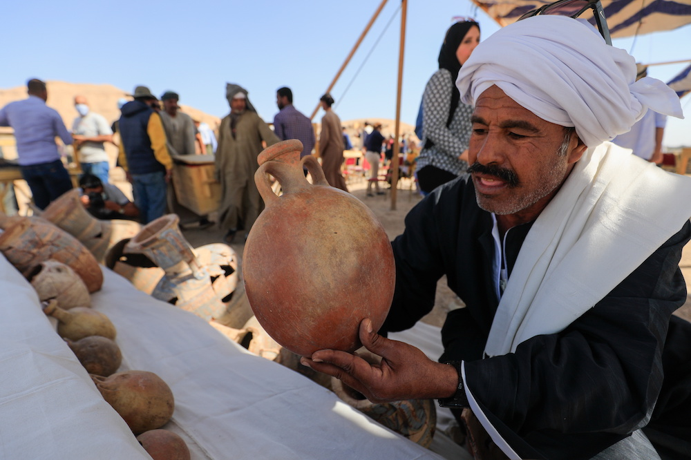 A man holds an unearthed pot at the site of the 'Lost Golden City', which was recently discovered by archaeologists, in the West Bank of Luxor, Upper Egypt, April 10, 2021. — Reuters pic