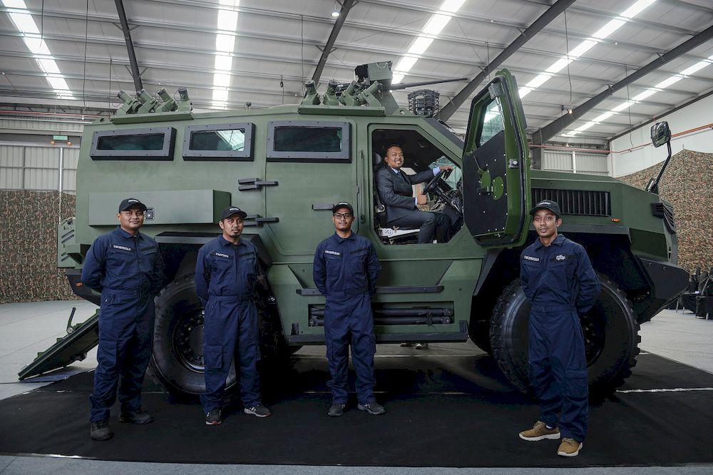 MILDEF Chief Executive Officer Datuk Seri Mohd Nizam Kasa with several crew members posing with the MILDEF HMAV4x4 armored car at MILDEF, Feb 11, 2021. — Bernama pic
