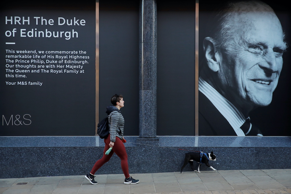 A woman walks past a shop with an image of Britain's Prince Philip, husband of Queen Elizabeth, who died at the age of 99, on the day of his funeral, in Windsor, near London, Britain, April 17, 2021. — Reuters pic