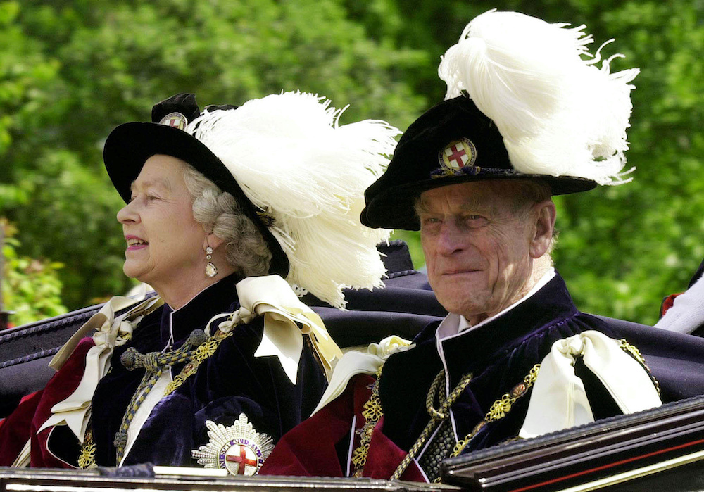 Britain's Queen Elizabeth II and Prince Phillip, the Duke of Edinburgh, wearing their Order of the Garter robes, ride in an open-topped carriage to Windsor Castle following the Garter Ceremony, June 18, 2001. — Reuters pic