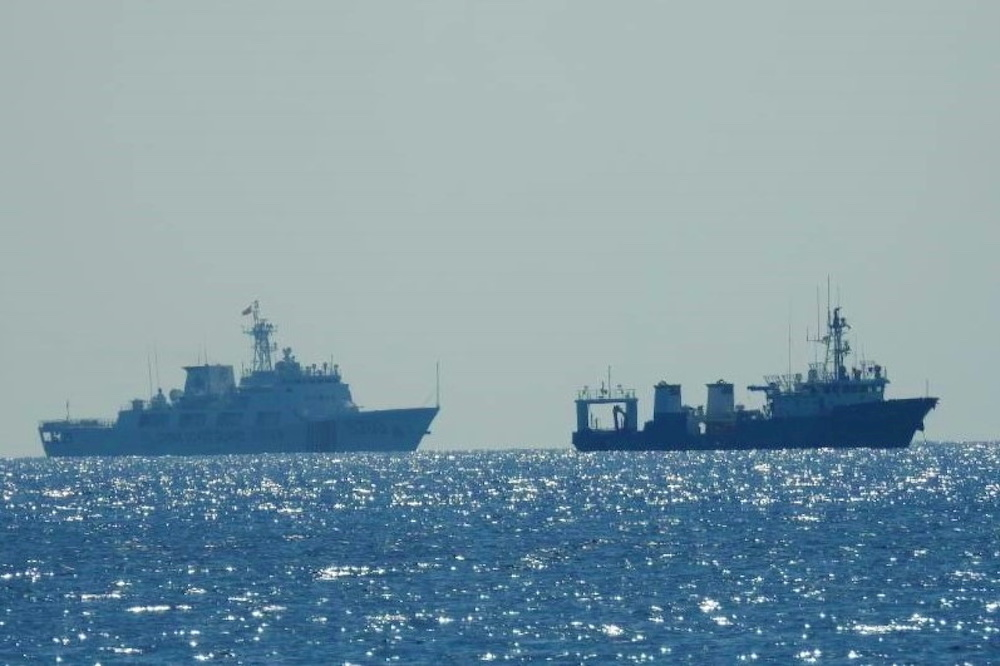 A Chinese Coast Guard patrol ship (left) is seen near an unidentified vessel at South China Sea, in a handout photo distributed by the Philippine Coast Guard April 15 and taken according to the source either on April 13 or 14, 2021. — Reuters pic