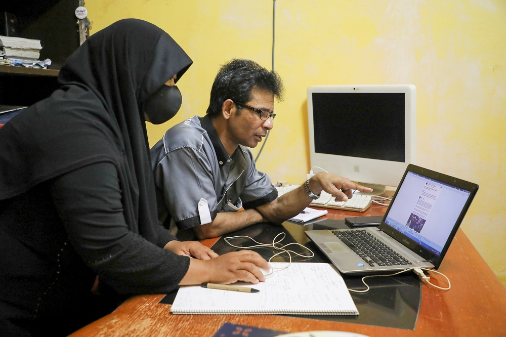 Rohingya refugee and activist Zafar Ahmad Abdul Ghani and his wife look at a computer screen displaying the threats and hate speech they received, at their home in Kuala Lumpur March 19, 2021. ― Reuters pic