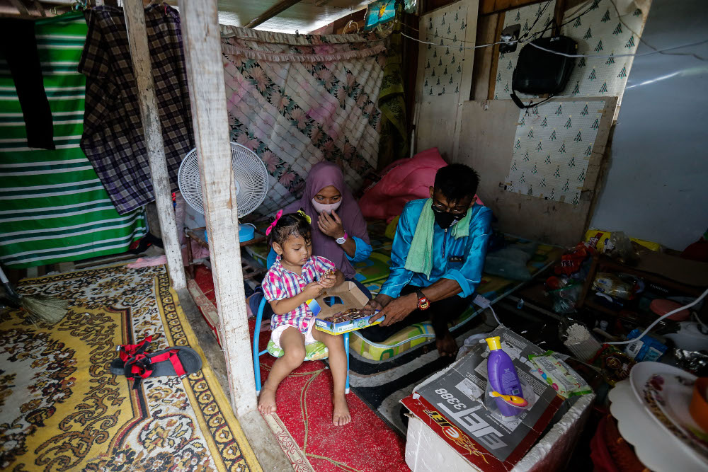 Effandy Abd Rahim and his wife Salbilla Supriyadi with their daughter Nuur Zulaieca sitting in their makeshift bedroom in a storeroom after their old house caught fire here at Lorong Sempadan Dua, Ayer Itam, April 19, 2021. — Picture by Sayuti Zainudin