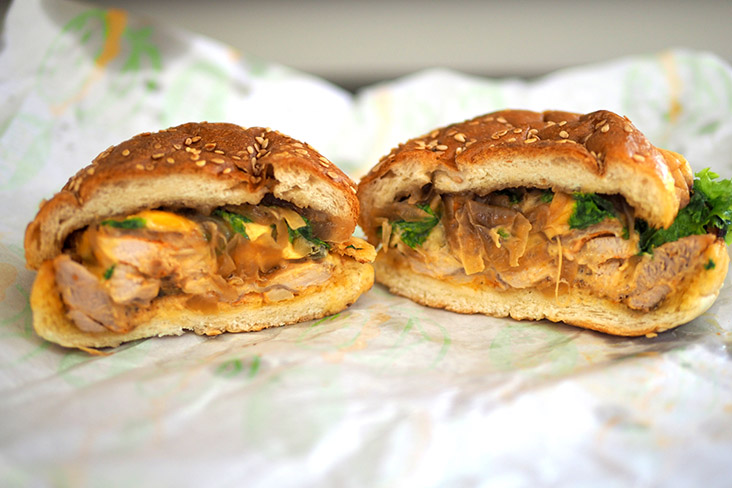 A cross section of the Cajun grilled chicken burger that has caramelised onions and vegetables with a soft brioche bun