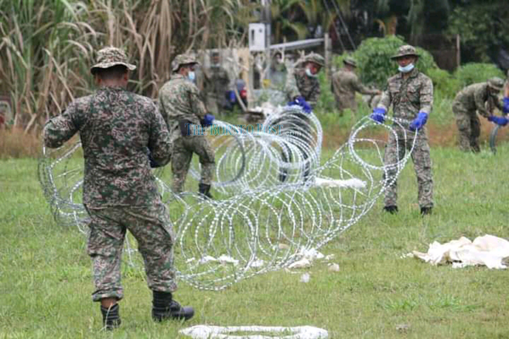 Members of the armed forces install the barbed wires around one of the EMCO-imposed areas in Bintulu. — Borneo Post Online file pic