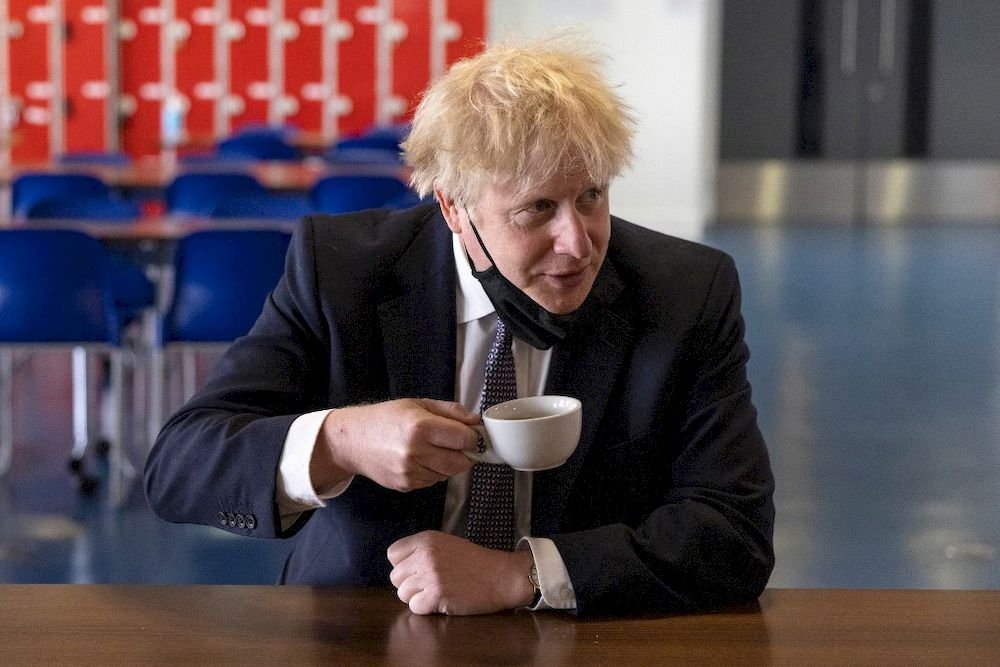 Britain's Prime Minister Boris Johnson, holds a cup of coffee as he speaks with pupils after taking part in a science lesson at King Solomon Academy in London, on April 29, 2021. — AFP pic