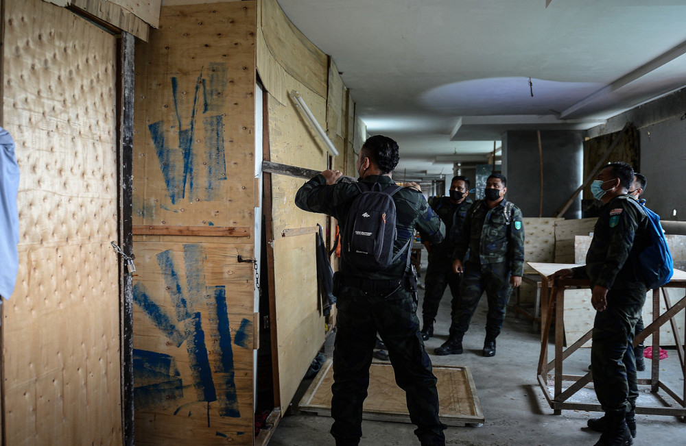 General Operations Force personnel try to break open a door during the Immigration Department's integrated operation at a construction site in Setapak, April 7, 2021. — Bernama pic