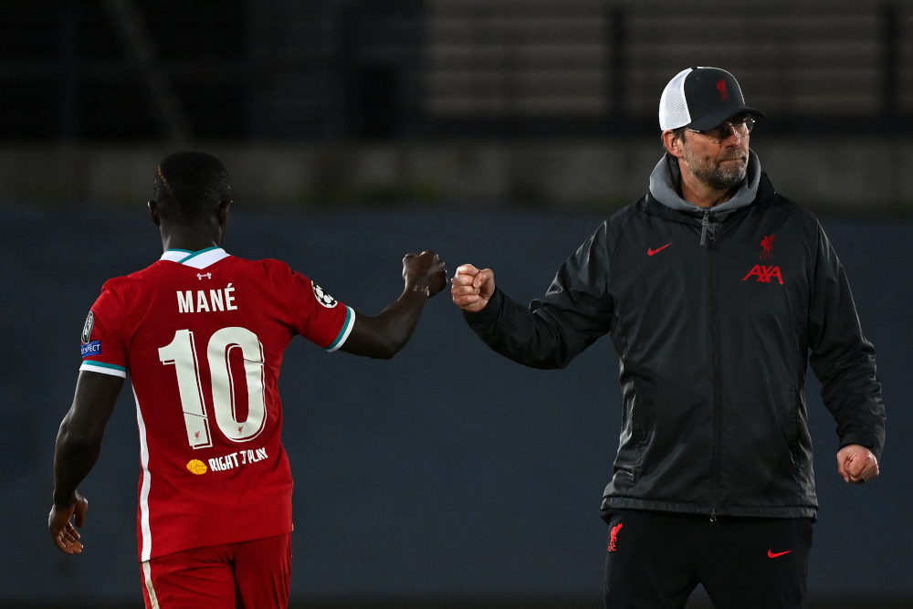 Liverpool manager Jurgen Klopp fist bumps striker Sadio Mane at the end of the Uefa Champions League first leg quarter-final football match against Real Madrid at the Alfredo di Stefano stadium in Valdebebas, April 6, 2021. — AFP pic