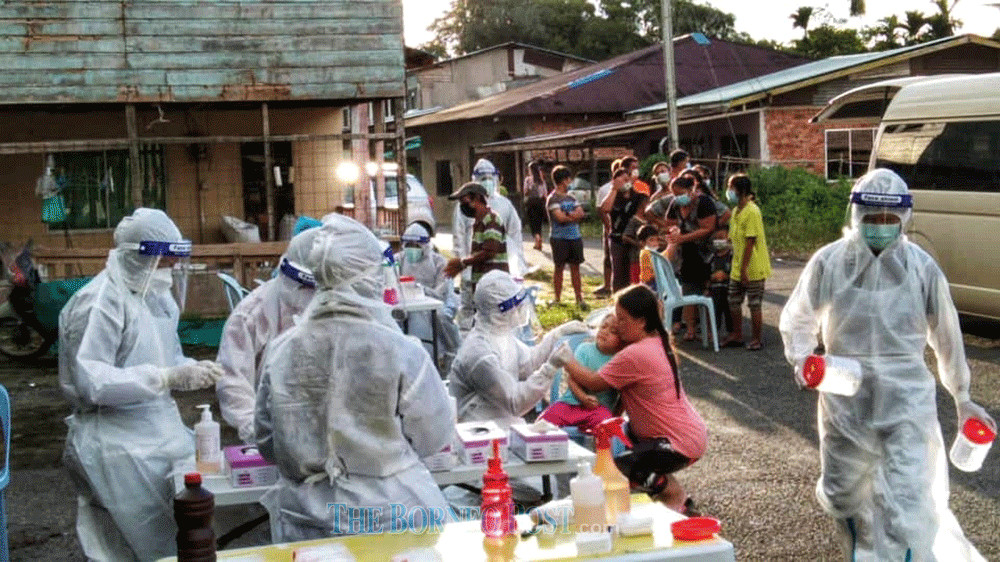A Covid-19 swab team in the thick of action carrying out sampling at a longhouse in Sibu recently. — Borneo Post Online pic
