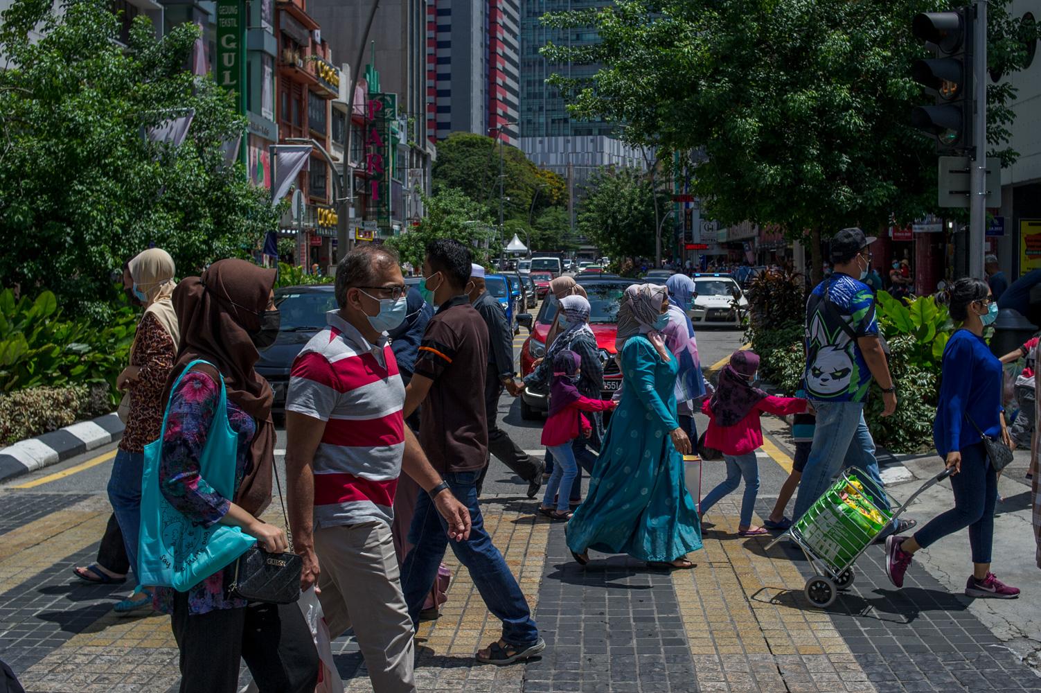 People wearing masks throng Jalan Tuanku Abdul Rahman to do some shopping in Kuala Lumpur April 18, 2021. — Picture by Shafwan Zaidon