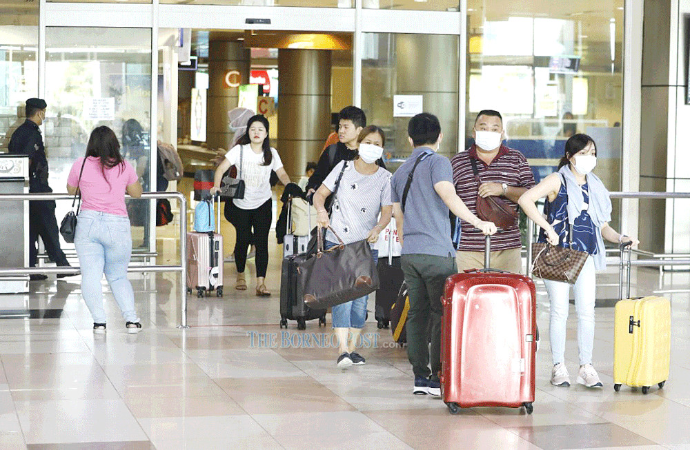 Photo shows several passengers — all of whom are wearing face masks — heading out of the arrival hall at Kuching International Airport. — Borneo Post Online pic
