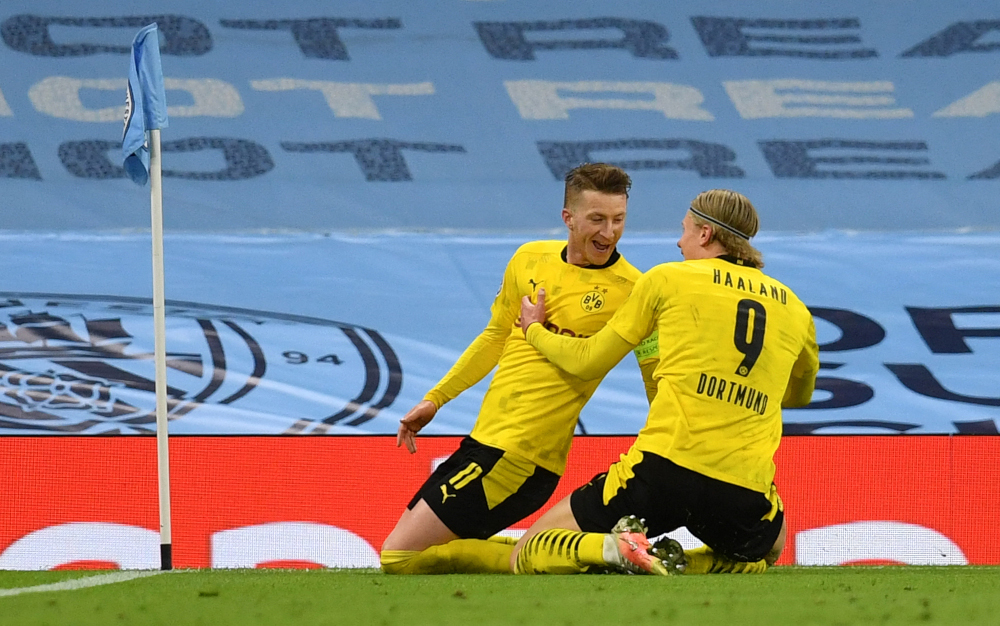 Dortmund forward Marco Reus celebrates after scoring the equalising goal with forward Erling Braut Haaland during the Uefa Champions League first leg quarter-final football match against Manchester City at the Etihad Stadium in Manchester, April 6, 2021. — AFP pic