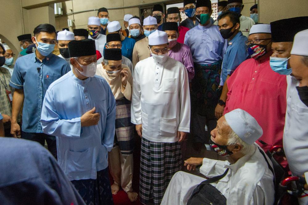 Prime Minister Tan Sri Muhyiddin speaks to a mosque congregant at Masjid Jamek Al-Amaniah, Batu Caves, April 19, 2021. With him is Gombak Member of Parliament Datuk Seri Mohamed Azmin Ali. — Picture by Shafwan Zaidon