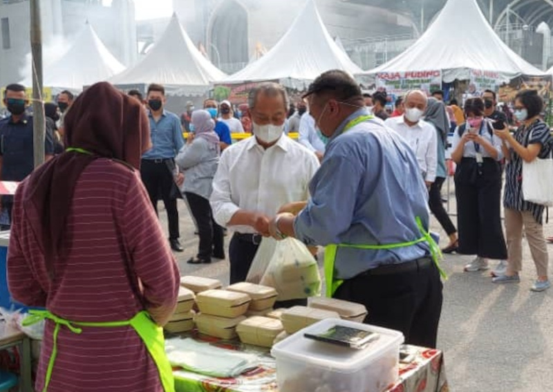 Prime Minister Tan Sri Muhyiddin Yassin was seen buying dishes such as 'kuih kaswi gula merah', 'laksa' and 'mee kolok' at the Ramadan bazaar in Putrajaya's Precinct 3, April 14, 2021. — Picture from Twitter/Bernamadotcom