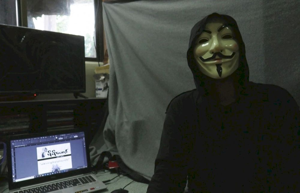 This screengrab provided via AFPTV video footage taken on April 10, 2021 shows Lynn Thant (an alias) wearing a mask next to a laptop where they are working on an underground newsletter to spread information in Yangon, amid internet outages as demonstrations continue against the military coup. — AFP pic