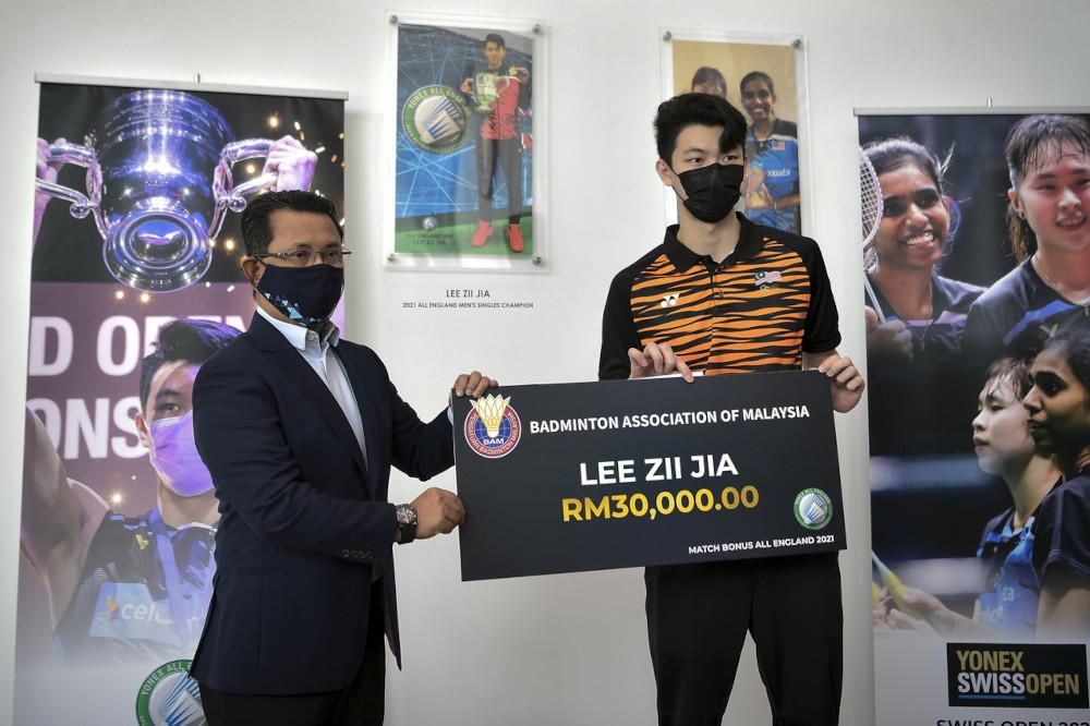 马羽总会长丹斯里诺扎移交3万令吉奖金的模拟支票,给新科全英赛冠军李梓嘉。-马新社-
