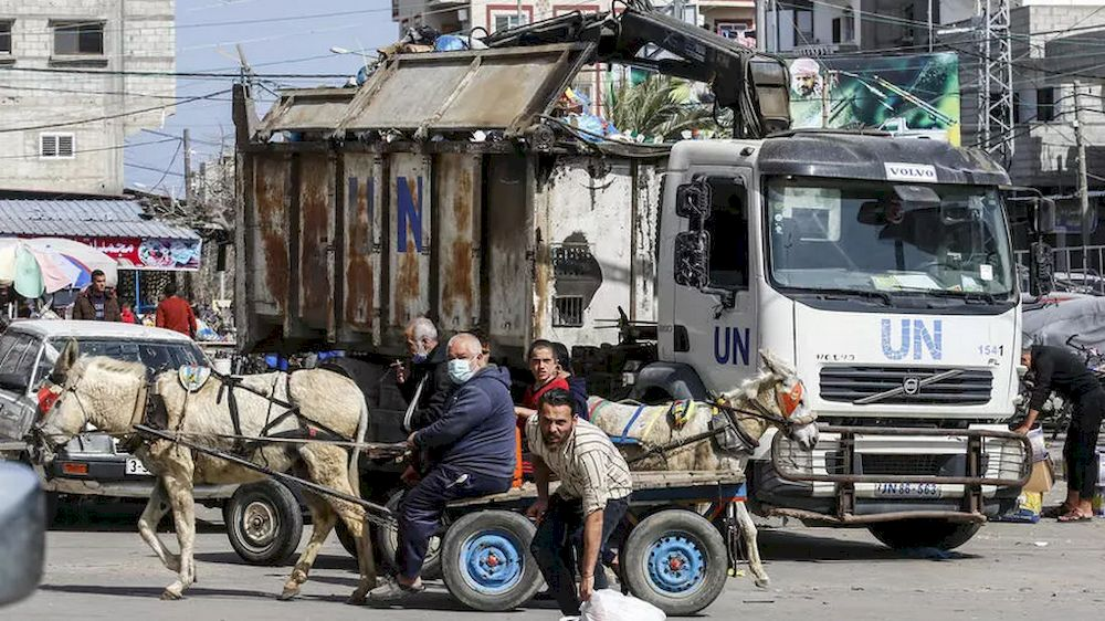 UNRWA workers clean a street at Rafah refugee camp in the Gaza Strip. — AFP pic