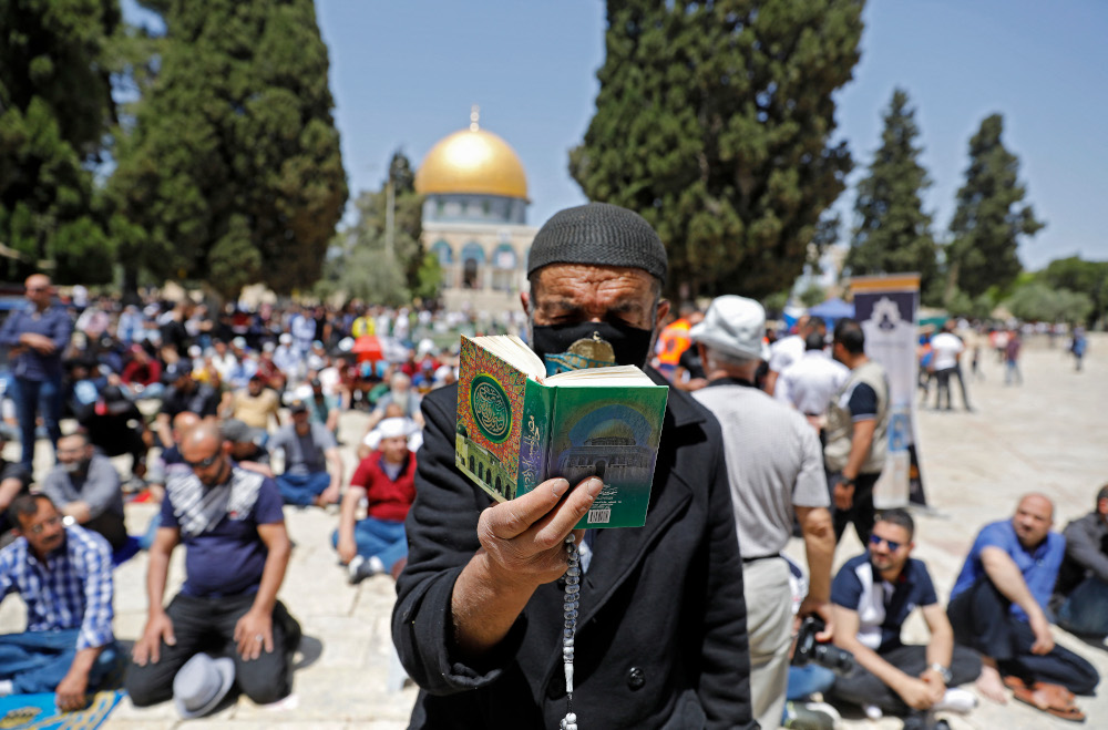 A man reads the Quran as Palestinians gather during the second Friday prayers of the Muslim fasting month of Ramadan, outside the Dome of the Rock at the Al-Aqsa Mosque compound, Islam's third holiest site, in Jerusalem's Old City, April 23, 2021. — AFP pic