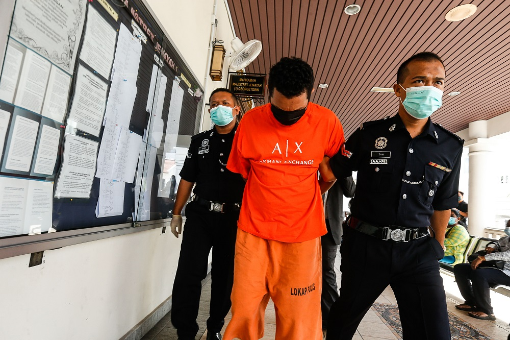 Mohd Arafat Taufik is escorted by policemen at the Magistrate's Court in George Town April 23, 2021. ― Picture by Sayuti Zainudin