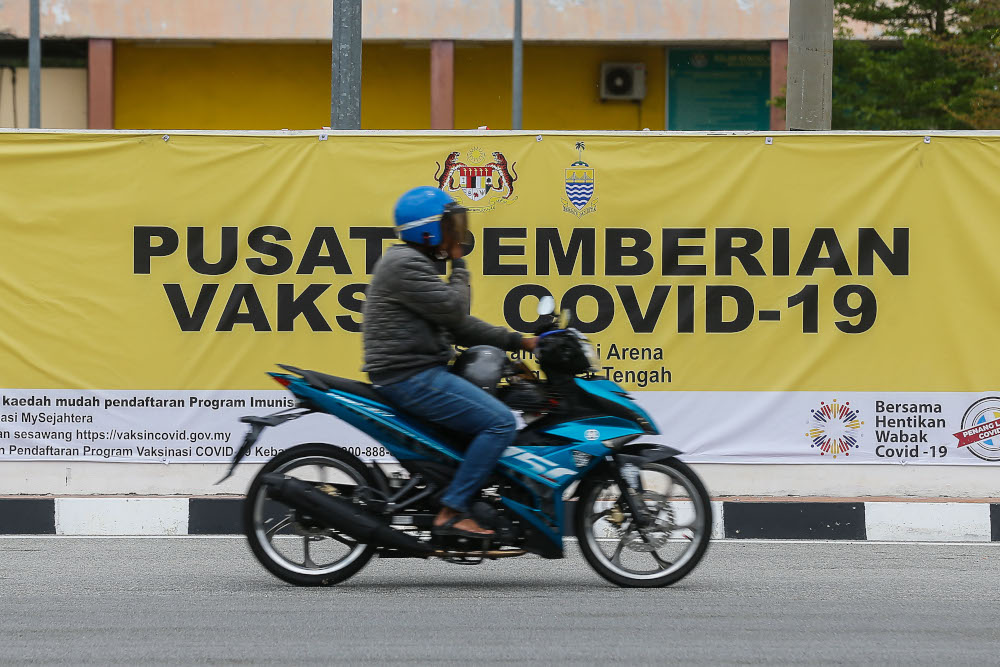 File picture shows a motorist riding past the Vaccine Administration Centre banner in Seberang Perai Arena, Seberang Jaya April 2, 2021. — Picture by Sayuti Zainudin