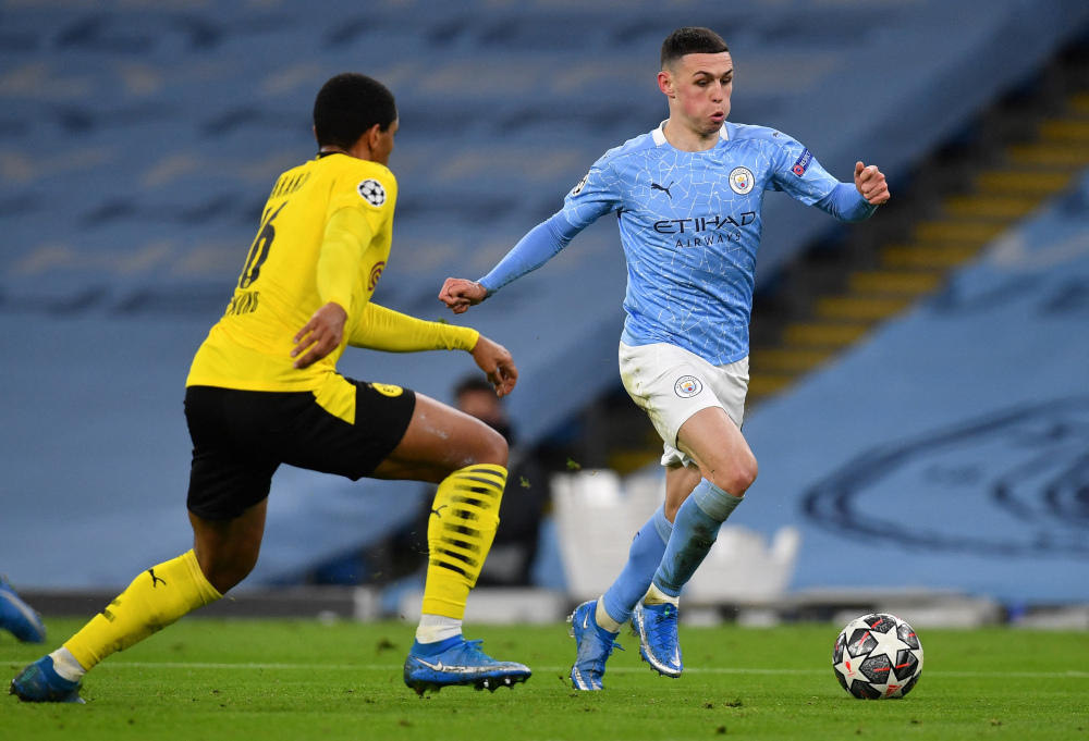 Dortmund defender Manuel Akanji vies with Manchester City's Phil Foden during the Uefa Champions League first leg quarter-final football match at the Etihad Stadium in Manchester, north west England, April 6, 2021. — Bernama pic