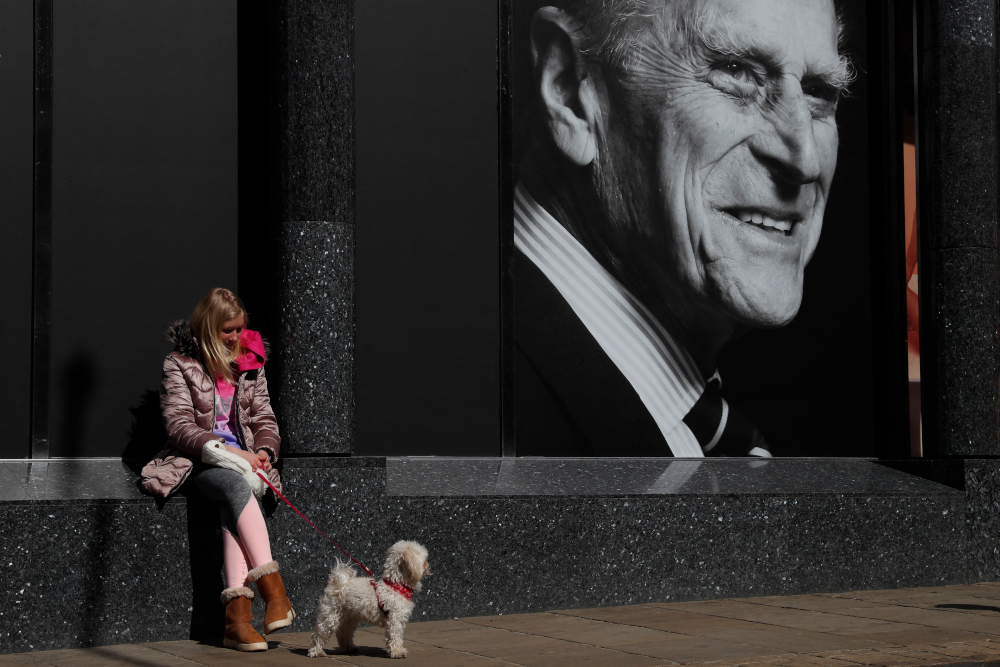 A woman and her dog sit outside a supermarket with a poster featuring Britain's Prince Philip, Duke of Edinburgh in the window, in the High Street of Windsor, west of London, April 16, 2021. — AFP pic