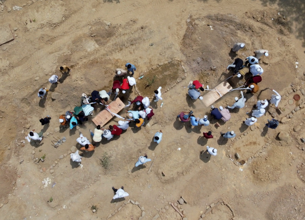 People bury the bodies of victims who died due to the coronavirus disease (Covid-19), at a graveyard in New Delhi April 16, 2021. Picture taken with a drone. — Reuters pic