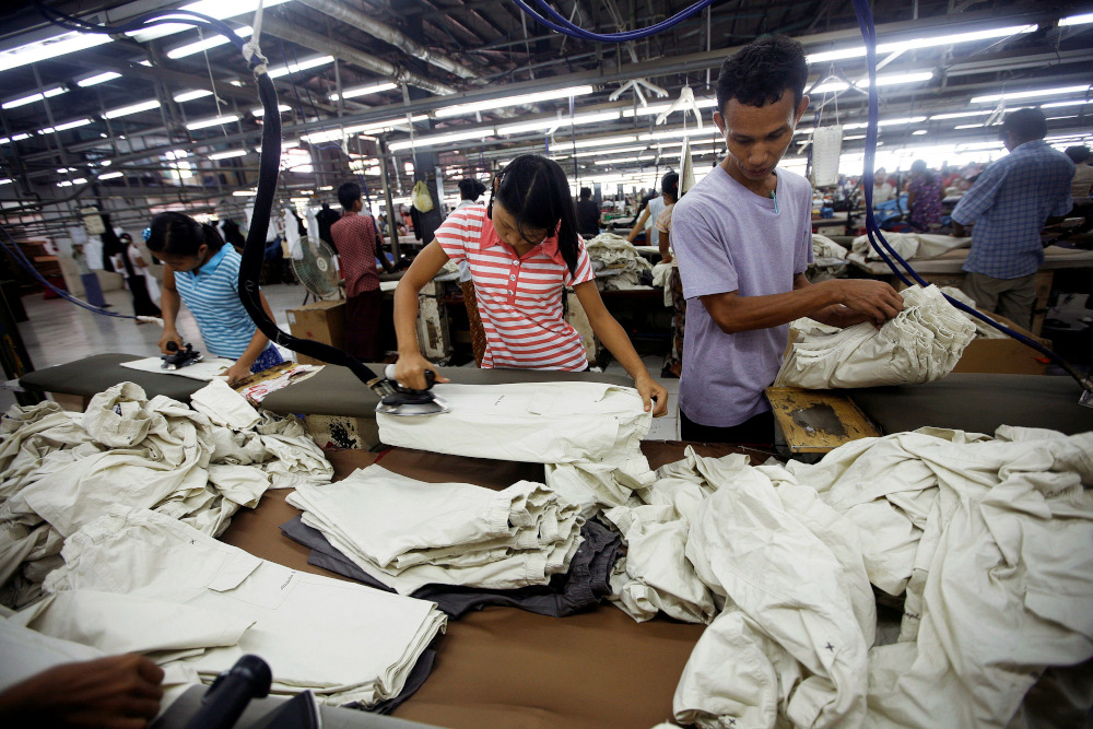 Workers iron and arrange clothing at a garment factory at Hlaing Taryar industrial zone in Yangon in this file picture taken on March 10, 2010. — Reuters pic