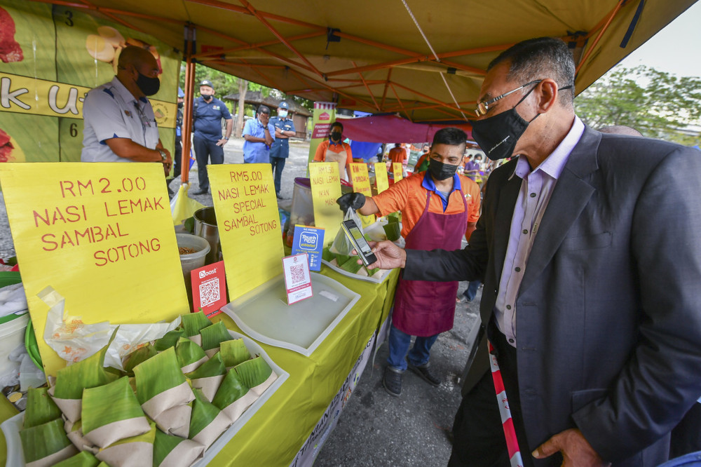 Deputy Domestic Trade and Consumer Affairs Minister Datuk Rosol Wahid scanning the QR code for the e-wallet application to buy 'nasi lemak' at the Putrajaya farmers' market, April 6, 2021. — Bernama pic