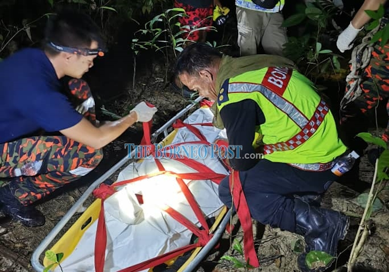Bomba personnel securing the deceased's body on a stretcher before it was brought out of the jungle April 11, 2021. — Borneo Post pic