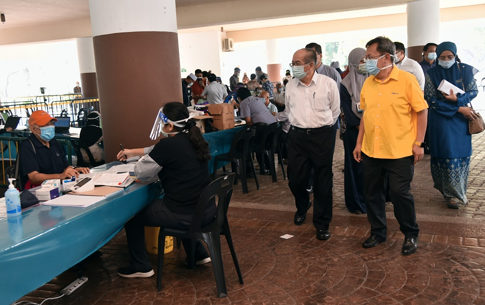 File picture of Sarawak Deputy Chief Minister Datuk Amar Douglas Uggah (second, right) observing the registration process of the vaccination programme at the Indoor Stadium, April 23, 2021. ― Picture courtesy of the state Information Department