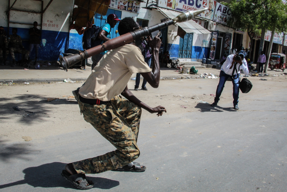 Photographers take pictures of a Somali military force member supporting anti-government while he poses on a street in Mogadishu, Somalia, April 25, 2021. — AFP pic