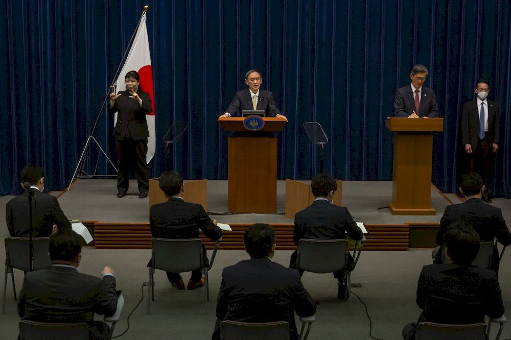 Japanese Prime Minister Yoshihide Suga (centre) speaks during a press conference in Tokyo on April 23, 2021, after the government announced a new coronavirus state of emergency covering Tokyo, Osaka, Kyoto and Hyogo regions. — AFP pic