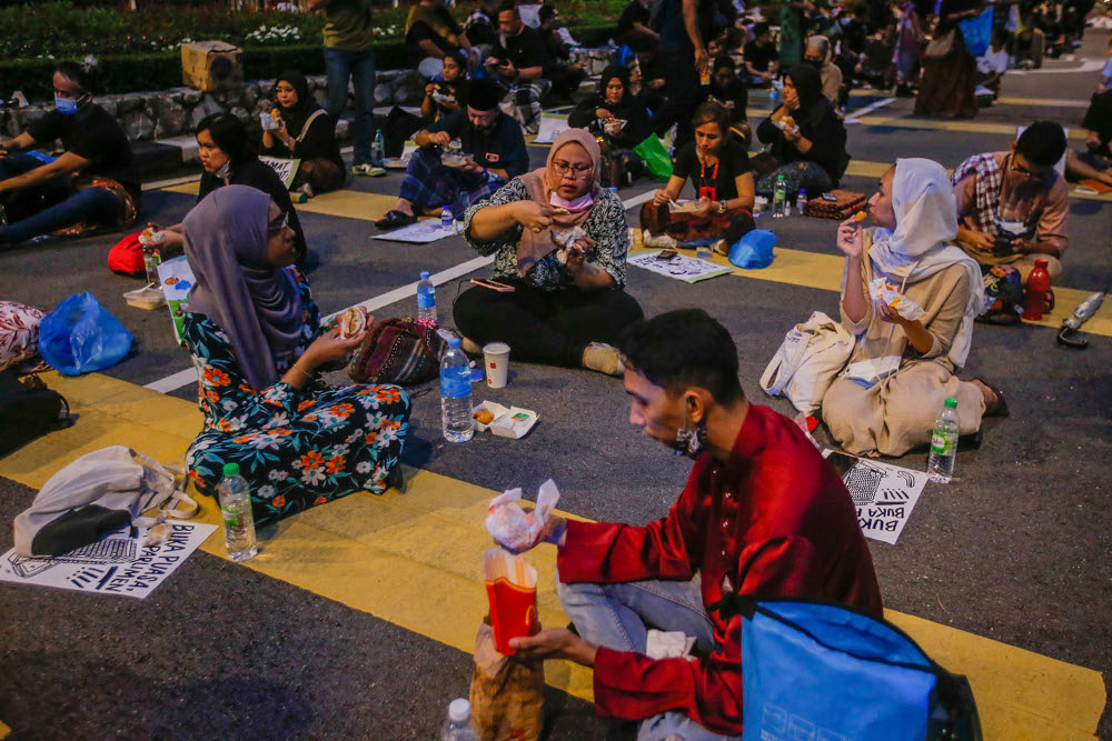 About a hundred Malaysian youths break their fast in front of the Parliament building, April 30, 2021. ― Picture by Hari Anggara