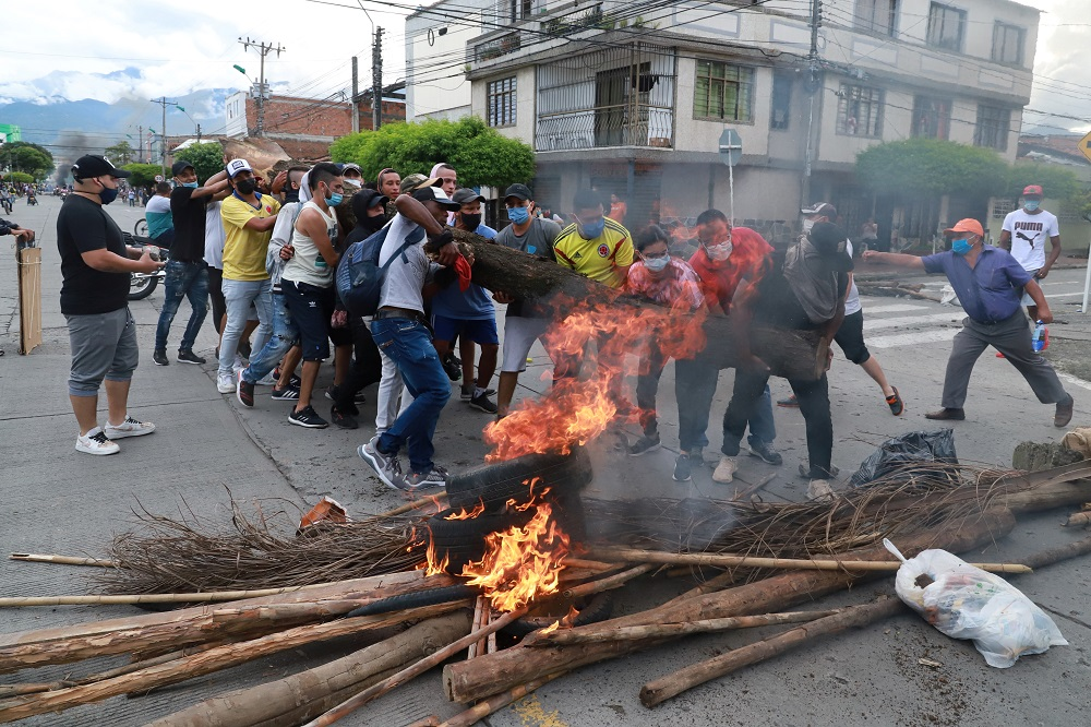 People carry a log of wood to build a barricade during a protest against what they say was police brutality exerted in recent protests against President Ivan Duque's government's tax reform in Cali, Colombia May 3, 2021. — Reuters pic