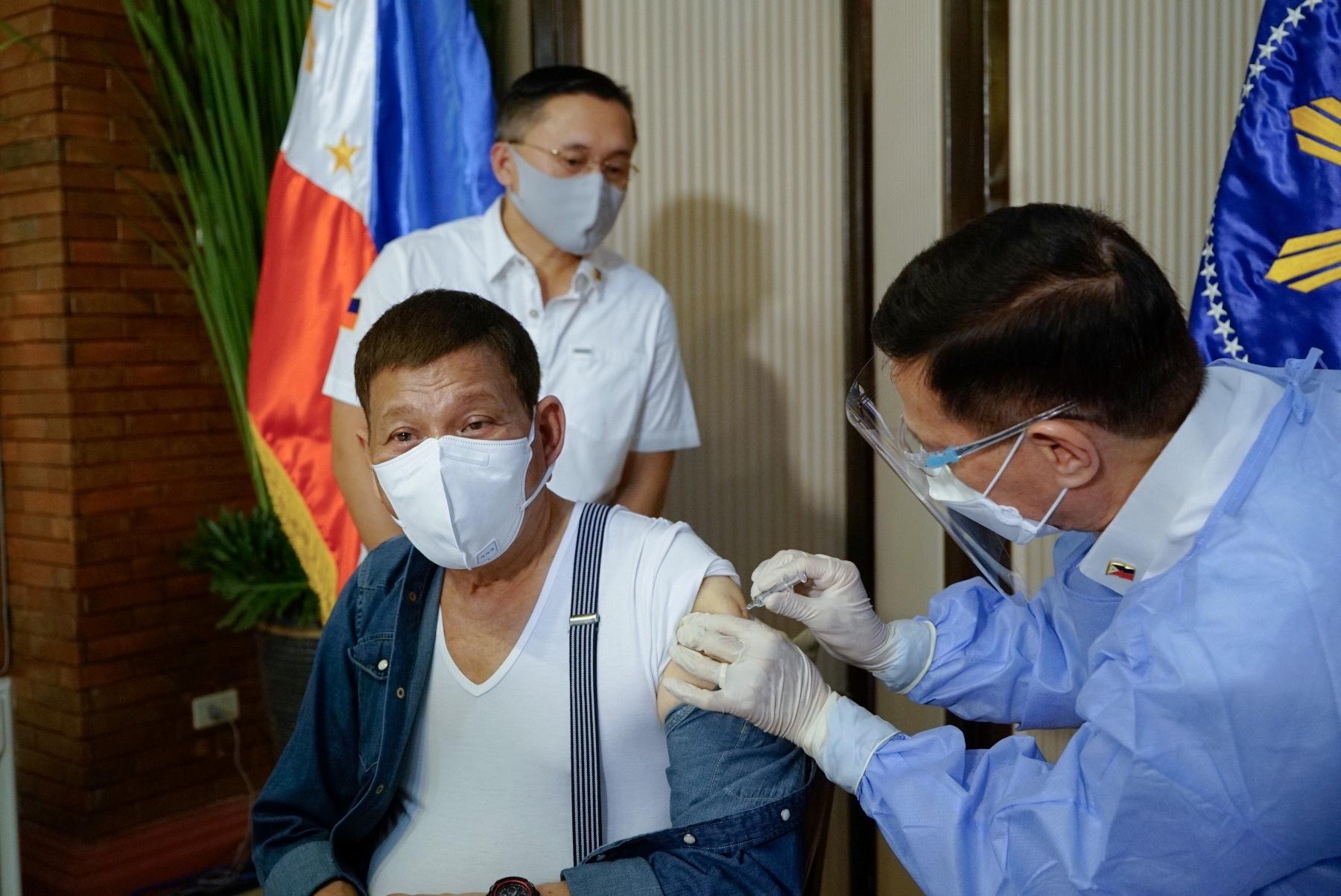 76岁的杜特尔特周一穿着白色汗衫,由菲国卫生部长杜克接种国药疫苗。-路透社-