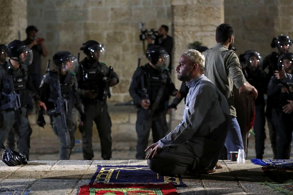 A Palestinian man prays as Israeli police gather during clashes at the compound that houses Al-Aqsa Mosque in Jerusalem's Old City May 7, 2021. — Reuters pic