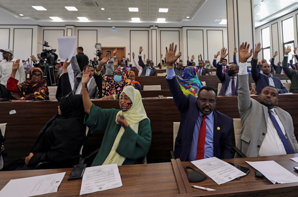 Somalia legislators vote by rising their hands to cancel a divisive two-year presidential term extension, inside the lower house of Parliament in Mogadishu, Somalia May 1, 2021. — Reuters pic