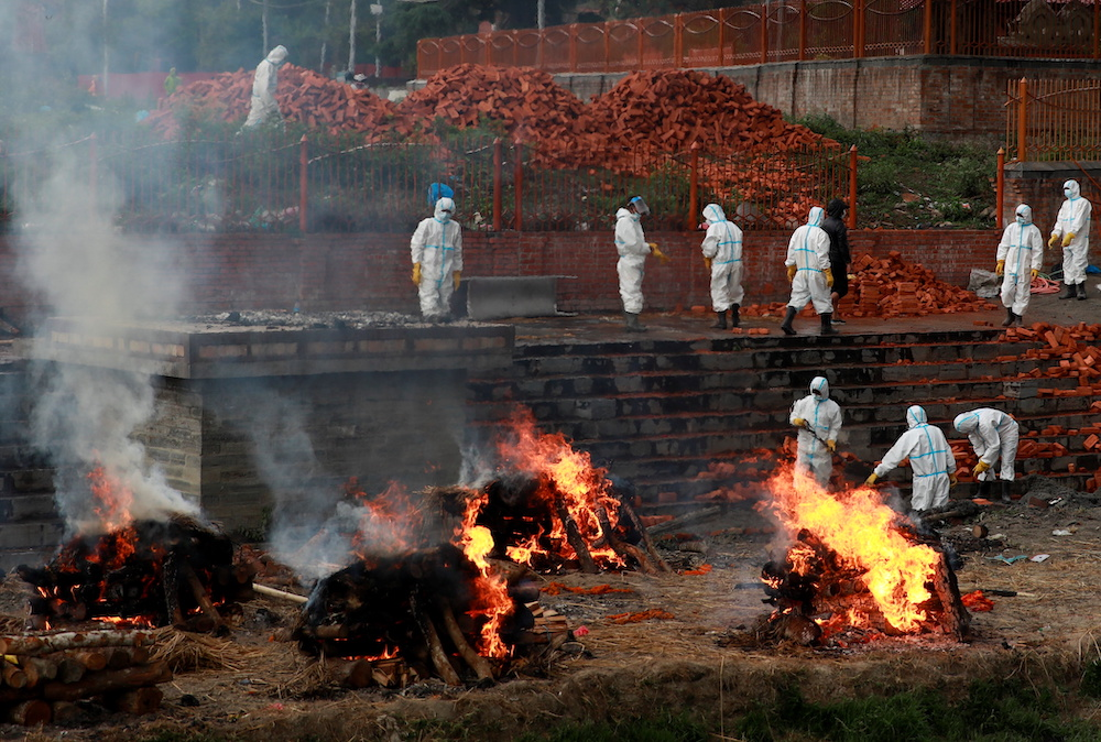 Workers wearing personal protective equipment (PPE) work to extend the crematorium as the number of people who died from coronavirus disease (Covid-19) surges, as India's outbreak spreads across South Asia, in Kathmandu, Nepal May 5, 2021. — Reuters pic