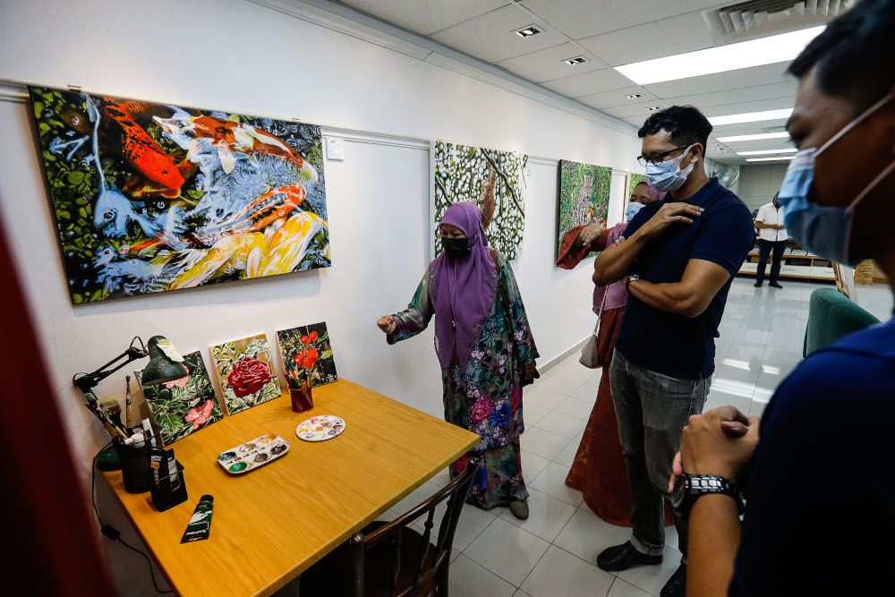 The family of the late Nasir Nadzir view some of the painting made by Nasir during the exhibition held at The Art Gallery, Pulau Tikus May 7, 2021. — Picture by Sayuti Zainudin